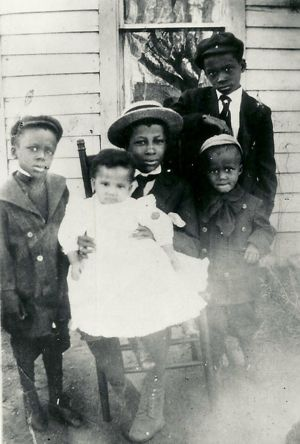 The Smiths:  Sitting in chair -Charles holding  Marguerite. Standing: Jessie, Vincent and Donald