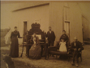 William Martindale Benson on far right.  Others in photo, left to right of first family:  Emma (daughter-in-law), daughter Mary Theodoshie at piano, son Samuel; Second family:  daughter Tressie Treene, Margaret Ann Fagan (2nd wife) and baby George Watters