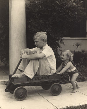 Lois pushing Willis in wagon.